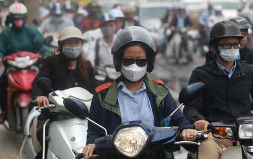 Người đi xe máy đeo khẩu trang tránh bụi trên đường Minh Khai. Ảnh: Tất Định