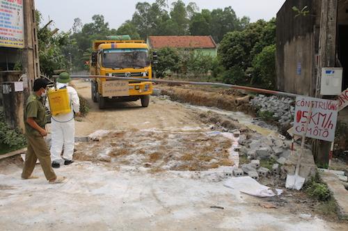 Cán bộ chuẩn bị phun hóa chất khử trùng khi xe qua chốt kiểm dịch tại xóm 7, xã Quỳnh Mỹ trưa 14/3. Ảnh: Nguyễn Hải.