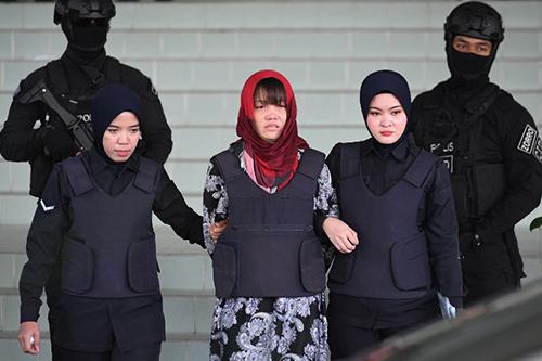 Cảnh sát áp giải Đoàn Thị Hương bên ngoài tòa án ở Kuala Lumpur, Malaysia hôm qua. Ảnh: AFP