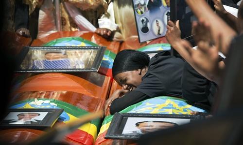 Người thân của các nạn nhân vụ rơi máy bay Ethiopian Airlines khóc bên những chiếc quan tài rỗng phủ quốc kỳ Ethiopia trong lễ tang tập thể ở thủ đô Addis Ababa ngày 17/3. Ảnh: AP.
