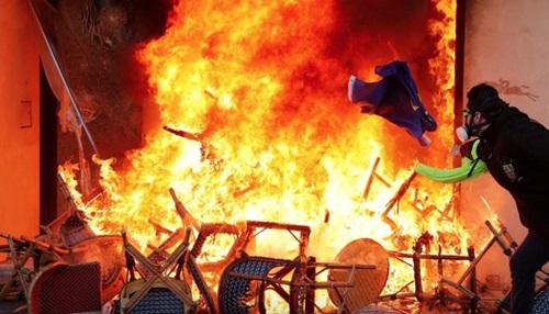 Người biểu tình ném lá cờ vào đám cháy tại một cửa hàng ở Paris hôm 16/3. Ảnh: Reuters.
