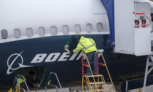 Nhân viên làm việc trên thân máy bay Boeing 737 MAX 9 tại nhà máy ở Washington ngày 14/3. Ảnh: AFP.