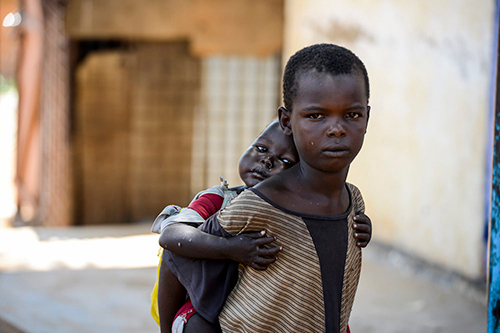 A child carries his younger sister on his back. Both children are living on the street in Aweil, South Sudan — Photo credit: UNICEF