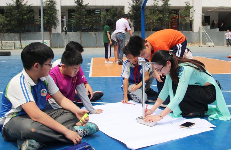 Cô giáo Hoàng Lan Phương hướng dẫn học sinh cách đo góc bóng mặt trời. Ảnh: Thùy Linh