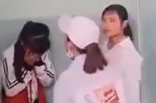 Nữ sinh lớp 7 (trái) bị vây đánh trong nhà vệ sinh ở Phú Yên, hôm 15/3. Ảnh: Cắt từ video