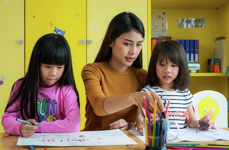 Giáo viên mầm non dạy trẻ vẽ. Ảnh: Pixels