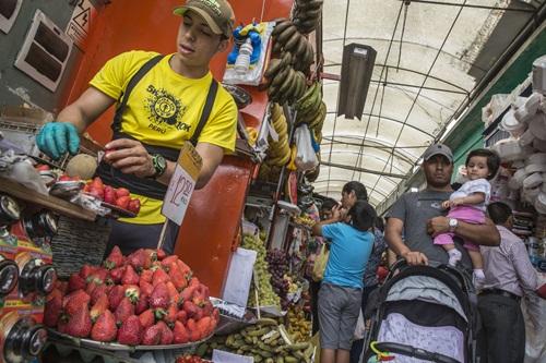 Wilmer Gonzales, người Venezuela, đã sống ở Peru hai năm, bán hoa quả tại chợ Magdalena. Ảnh: WSJ.