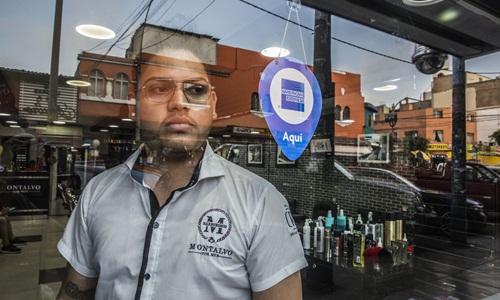 Oscar Villarroel, người Venezuela, chuyển tới sống ở Peru 4 năm trước, hiện mở một cửa hàng cắt tóc tại thủ đô Lima. Ảnh: WSJ.
