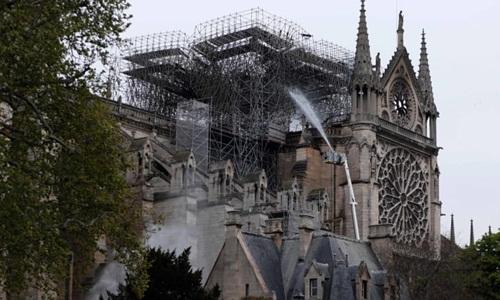 Lính cứu hỏa phun nước dập tắt đám cháy tại Nhà thờ Đức Bà Paris ngày 16/4. Ảnh: AFP.