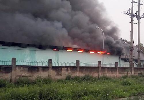 Lửa cùng ngọn khói bốc lên tại vụ cháy nhà kho công ty dược. Ảnh: Gia Chính.