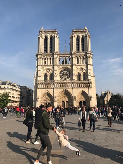 Hai cha con vui đùa bên ngoài Nhà thờ Đức Bà Paris chỉ một tiếng trước vụ hỏa hoạn ngày 15/4. Ảnh: Twitter.