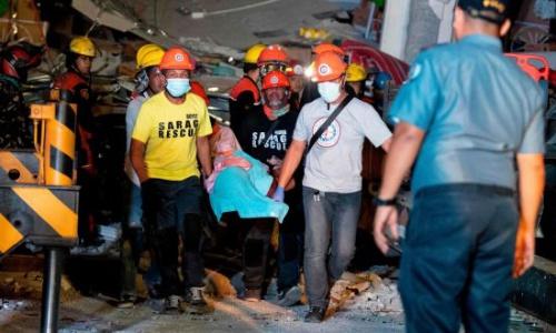Cứu hộ Philippines đưa người bị thương ra khỏi toà nhà bị sập trong động đất ngày 22/4. Ảnh: AFP.