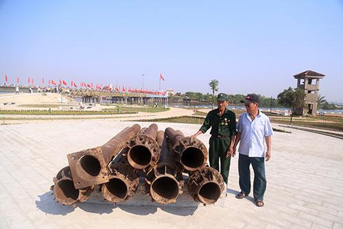 Ông Thoa (bên phải) tham quan phần còn lại của cột cờ bờ nam được trưng bày ở di tích đôi bờ Hiền Lương - Bến Hải. Ảnh: Hoàng Táo