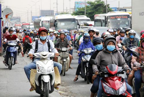 Người dân các tỉnh miền Tây quay lại TP HCM bằng xe máy trên Quốc lộ 1. Ảnh: Duy Trần