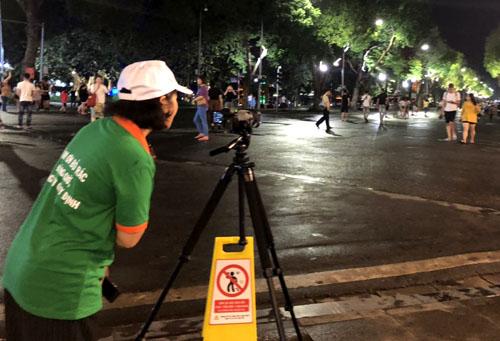 Nhân viên công ty môi trường ghi hình người xả rác bừa bãi ở phố đi bộ Hồ Gươm. Ảnh: N.H