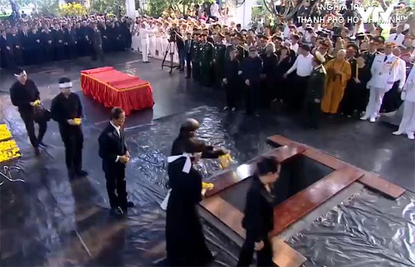 Mọi người thả hoa xuống huyệt mộ tiễn biệt nguyên Chủ tịch nước Lê Đức Anh. Ảnh: Hữu Khoa.