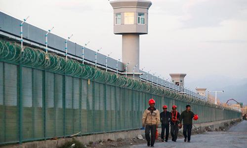 Công nhân đi bộ qua hàng rào tại nơi Trung Quốc gọi là trung tâm giáo dục nghề ở quận Đạt Phản Thành, thành phố Urumchi, khu tự trị Tân Cương, hôm 4/9/2018. Ảnh: Reuters.