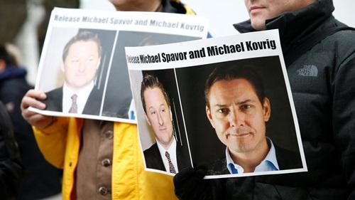 Người biểu tình cầm ảnh kêu gọi Trung Quốc trả tự do cho Michael Spavor (trái) và Michael Kovrig  trên đường phố Canada hồi tháng ba. Ảnh: Reuters.