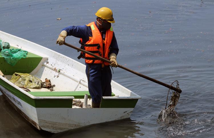 Công nhân công ty thoát nước Hà Nội dọn rác trên sông Tô Lịch. Ảnh: Võ Hải.