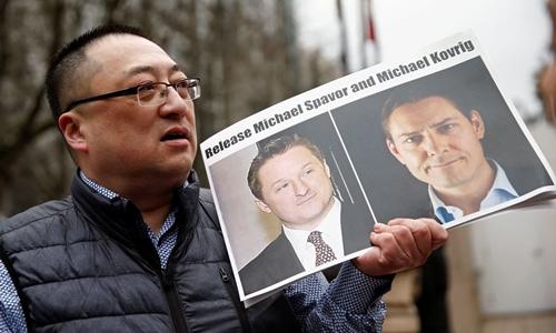Một người biểu tình ở Canada cầm ảnh của Spavor (trái) và Kovrig (phải), yêu cầu trả tự do cho hai người. Ảnh: Reuters.