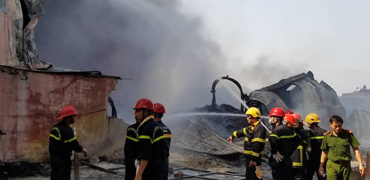 Lực lượng chức năng phun nước dập lửa. Ảnh: Giang Chinh