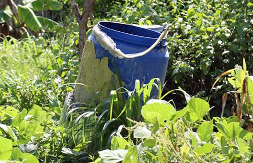Bình nhựa mà nhóm nghi can dùng để ướp xác nạn nhân nằm trong vườn căn nhà ở xã Hưng Hòa. Ảnh: Phước Tuấn.