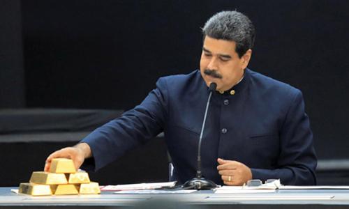 Tổng thống Venezuela Nicolas Maduro đặt những thỏi vàng lên bàn trong cuộc họp tại thủ đô Caracas hôm 22/3. Ảnh: Reuters.