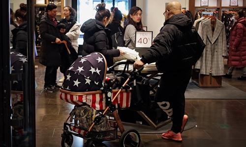 Một người Trung Quốc đẩy xe nôi có hình cờ Mỹ. Ảnh: AP.