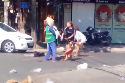 Cô gái chủ shop áo quần cầm chổi và dùng tay đánh bay nón của nữ lao công. Ảnh: Chụp màn hình