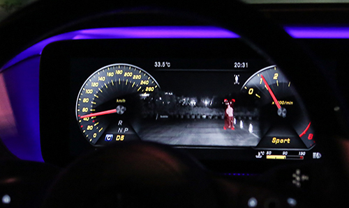 Màn hình sau vô-lăng xe Mercedeshiển thị cảnh báo có người di ở hướng xe đi tới.