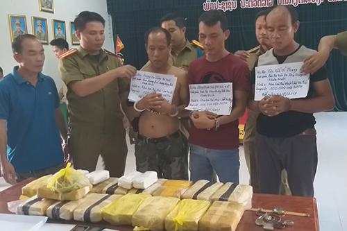Ba người Lào cùng tang vật được bọc trong các gói nilông. Ảnh: Quang Thuyên