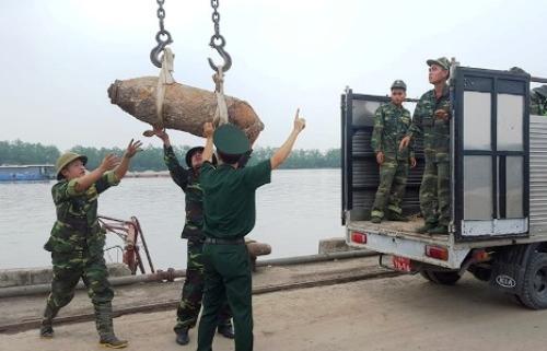 Lực lượng công binh Hải Phòng di dời quả bomb nặng 227kg được 2 bố con anh Trần Văn Cường phát hiện, vớt lên thuyền trong quá trình đi rà phế liệu trên sông Cấm. Ảnh:T.Tr