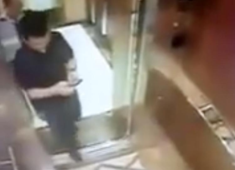Ông Nguyễn Hữu Linh dán mắt vào điện thoại trước khi thấy bé gái trong thang máy.