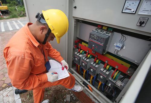 Nhân viên EVN Hà Nội ghi lại các thông số của trạm biến áp. Ảnh: Ngọc Thành.