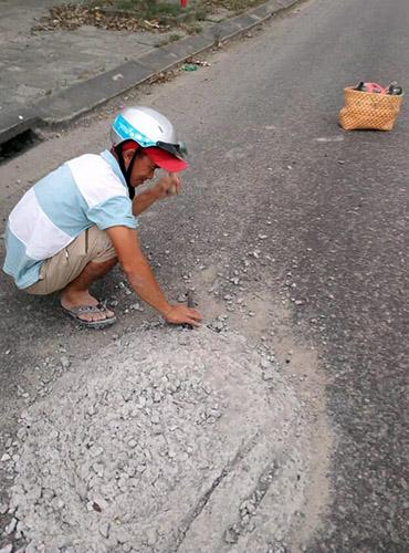 Anh Hùng dừng xe bên đường để đục bỏ ụ bê tông. Ảnh: Văn Cảnh.