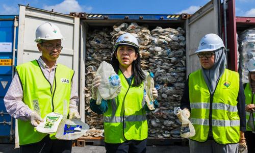 Bộ trưởng Yeo Bee Yin (giữa) đứng trước các container chứa rác thải nhựa tạicảng Klang hôm nay. Ảnh: AFP.