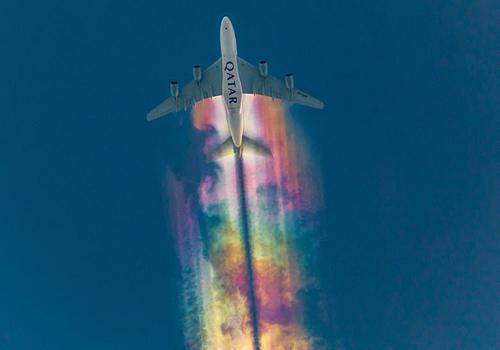 Vệt mây cầu vồng rực rỡ phía sau máy bay Qatar Airways. Ảnh:  Nick Beyersdorf.