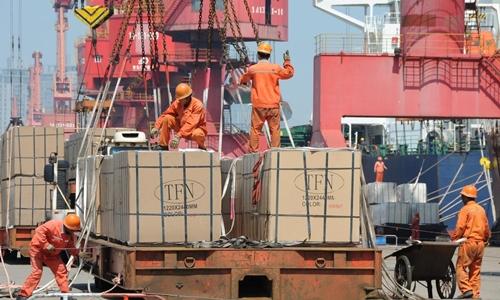 Công nhân xếp hàng xuất khẩu lên cần cẩu tại bến cảng thành phố Liên Vận Cảng, tỉnh Giang Tô, Trung Quốc hôm 7/6. Ảnh: Reuters.