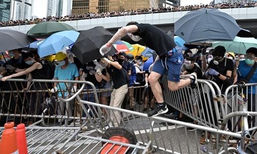 Người biểu tình dùng ô chống lại hơi cay của cảnh sát khi tiếp cận trụ sở Hội đồng Lập pháp Hong Kong. Ảnh: AFP.