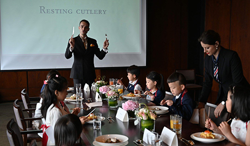 Guillaume de Bernadac hướng dẫn các học viên nhí cách dùng dao, dĩa trong bữa ăn. Photo: AFP