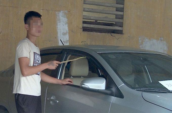 Phạm Văn Đô trong buổi dựng lại hiện trường đập kính xe ôtô. Ảnh. Cơ quan điều tra
