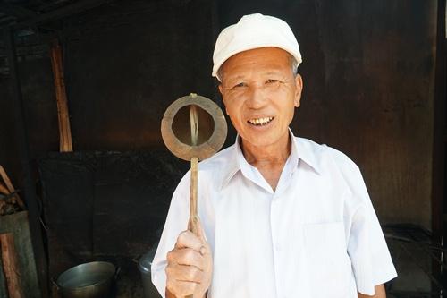 Ông Cẩm với chiếc gáo dừa tự làm cho vợ bán don. Ảnh: Phạm Linh.