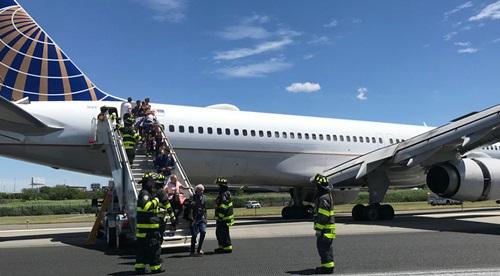 Lính cứu hỏa hỗ trợ hành khách sơ tán tại sân bay quốc tế Newark Liberty ở bang New Jersey chiều 15/6. Ảnh: Twitter.