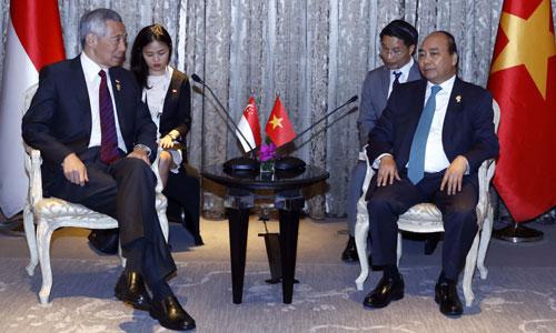 Thủ tướng Nguyễn Xuân Phúc (phải) gặp Thủ tướng Singapore Lý Hiển Long bên lề Hội nghị Cấp cao ASEAN lần thứ 34 tại Bangkok, Thái Lan chiều 22/6. Ảnh: TTXVN .