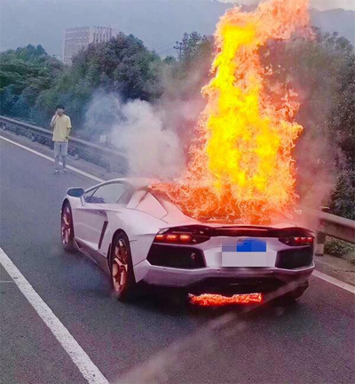 Tài xế (áo vàng) chỉ biết đứng nhìnkhi siêu xe bốc cháy mà không thể làm gì khác.