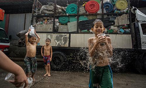 Trẻ em chơi đùa với các cốc và bình nhựa bên ngoài một cơ sở phân loại rác ở làng Canumay West Ảnh: Guardian