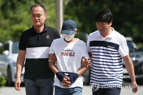 Nghi phạm đánh vợ Việt (giữa) bị cảnh sát Hàn Quốc áp giải hôm 8/7. Ảnh: Yonhap.