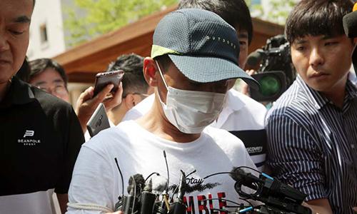 Nghi phạm đánh vợ Việt (giữa) bị áp giải ra tòa án thành phố Gwangju, tỉnh Jeollan Nam hôm 8/7. Ảnh: Korea Times.