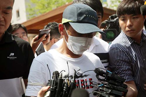 Nghi phạm đánh vợ Việt (giữa) bị áp giải ra tòa án thành phố Gwangju, tỉnh Jeollan Nam hôm 8/7. Ảnh: Korea Times