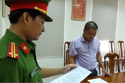 Đặng Vũ Thái (phải) nghe quyết định khởi tố vụ án, khởi tố bị can.Ảnh:Trần Tuấn